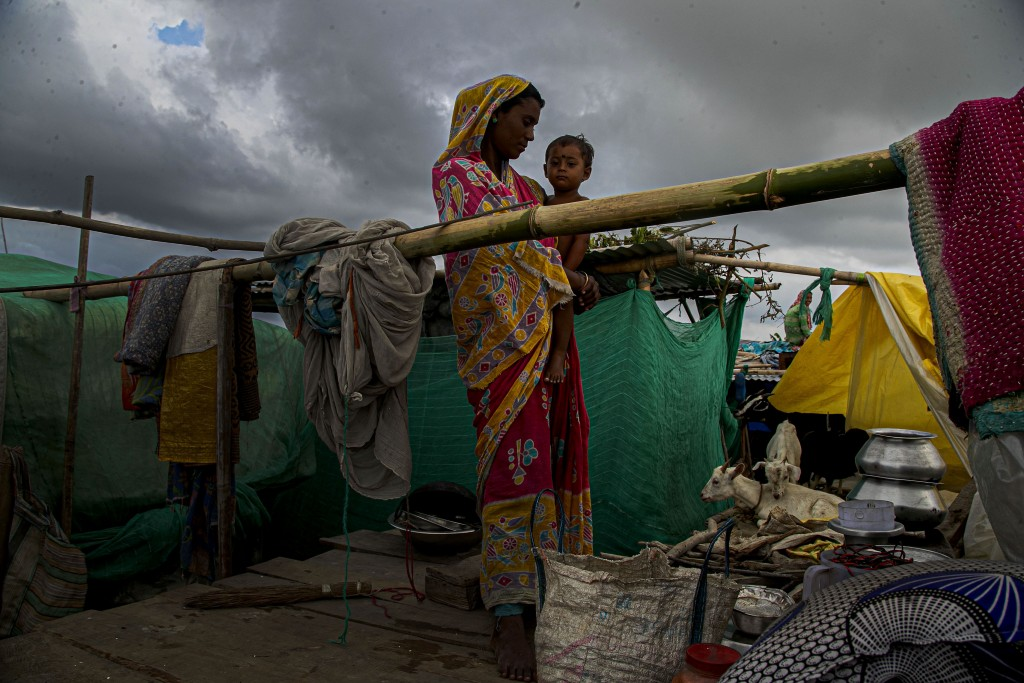 A flood affected woman and child take shelter at temporary structure near their submerged house along river Brahmaputra in  Morigaon district, Assam, ...