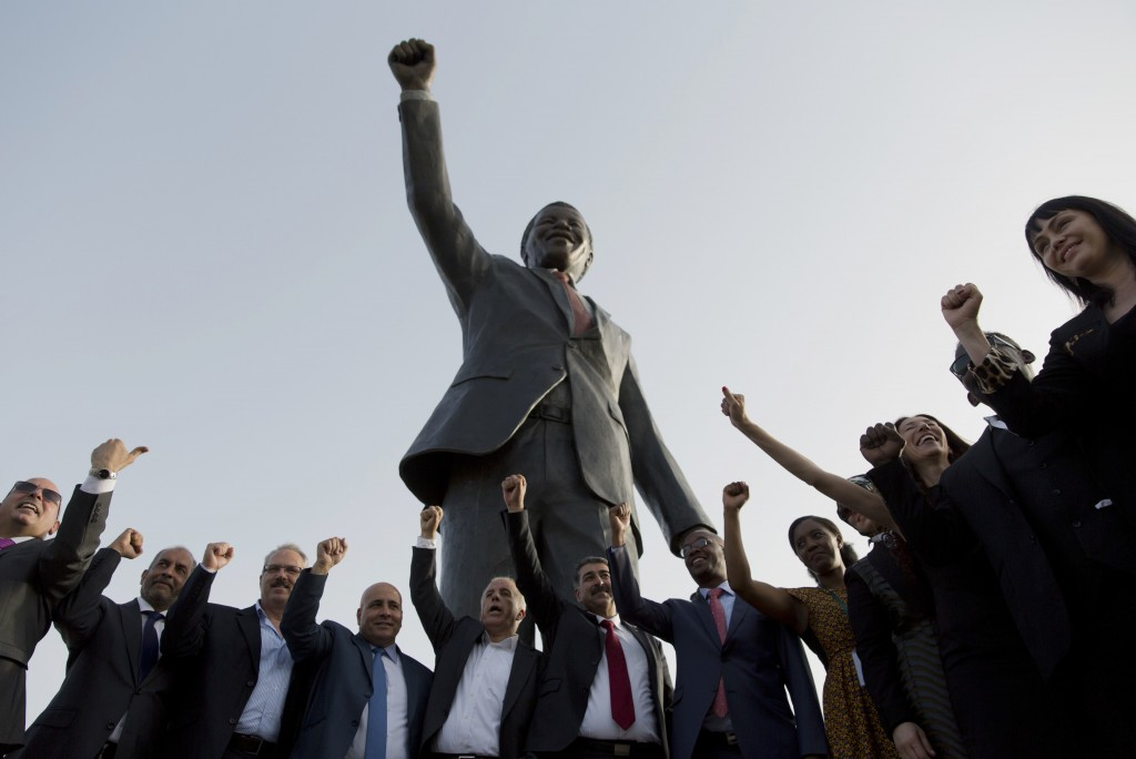 FILE - In this April 26, 2020 file photo, Palestinians pose at a sculpture of the first democratically elected South African president and anti aparth...