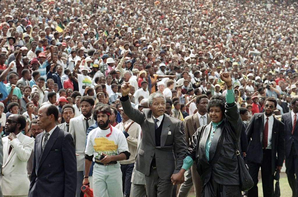 FILE - In this Feb. 13, 1990 file photo, Nelson Mandela, center left, and his wife Winnie, center right, raise clenched fists as they arrive at a welc...