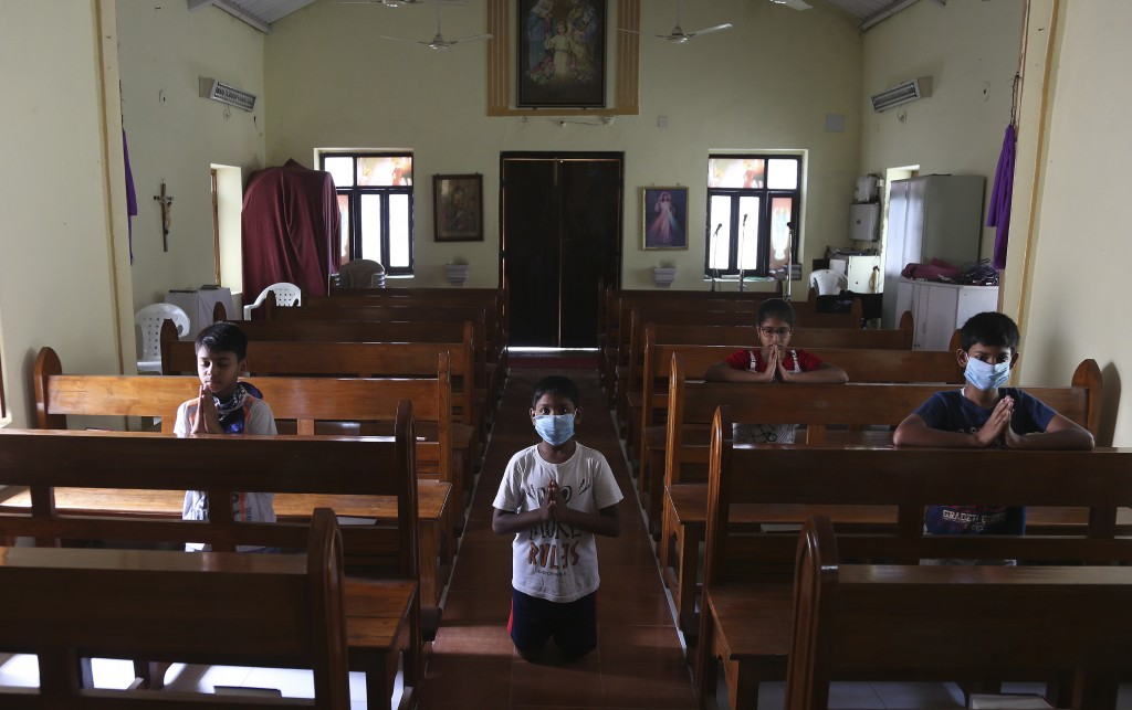 Catholic devotees offer prayers at Our Lady of Lourdes Church on Good Friday, during a lockdown to control the spread of the coronavirus in Hyderabad,...