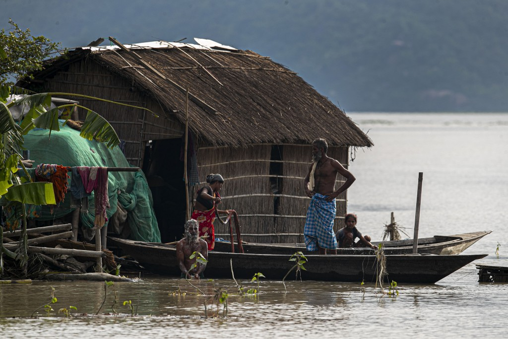 A flood affected family take shelter on boat near their partially submerged house along river Brahmaputra in Morigaon district, Assam, India, Thursday...