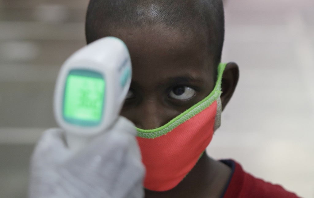 A health worker checks the body temperature of a boy at a medical camp to screen residents for COVID-19 symptoms in Mumbai, India, Friday, July 17, 20...