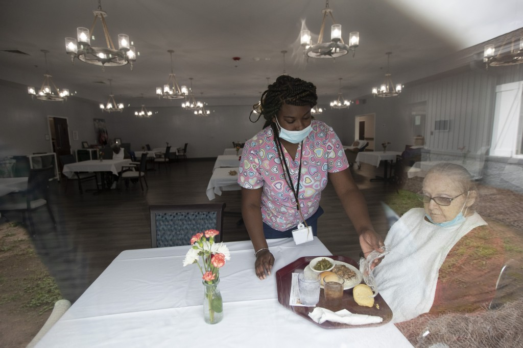 A staff member at Southern Pines nursing home helps a resident with her lunch Thursday, June 25, 2020, in Warner Robins, Ga. Residents are spaced out ...