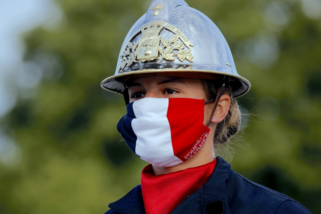 FILE - In this July 14, 2020, file photo, a firefighter wears a face mask with the colors of the French flag, prior to the Bastille Day parade on the ...