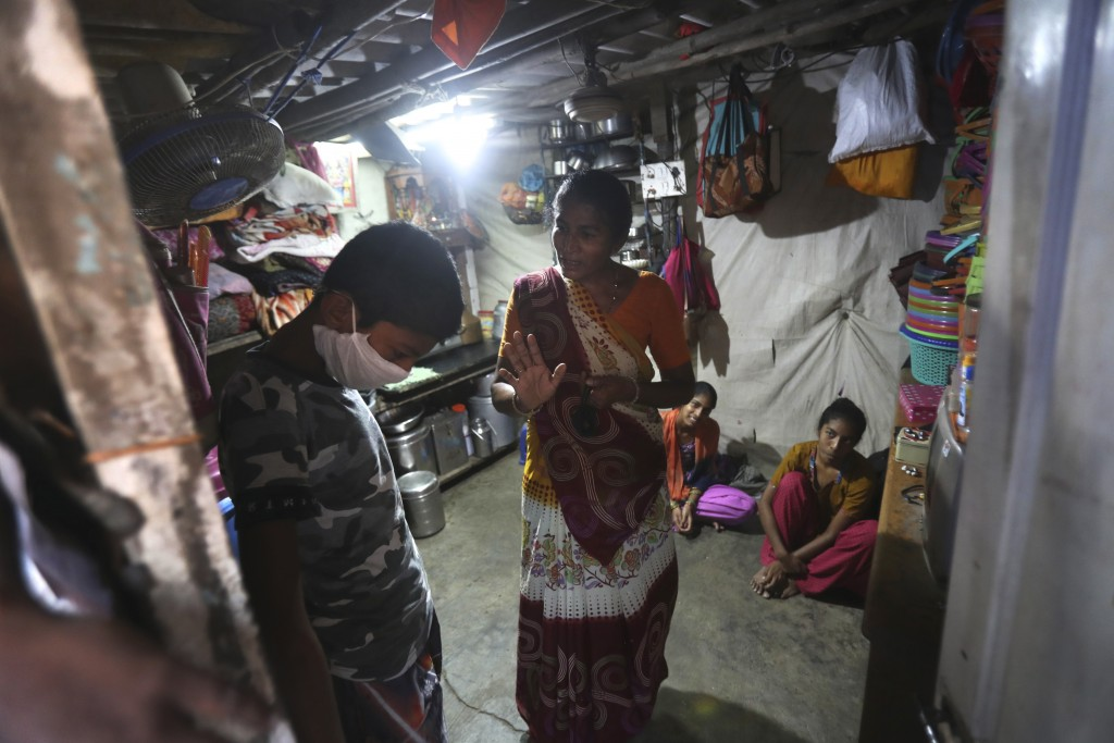 Mina Ramesh Jakhawadiya, center, tells her son Ritik Ramesh, left, not to go out and play because of the coronavirus and be in the house in Mumbai, In...