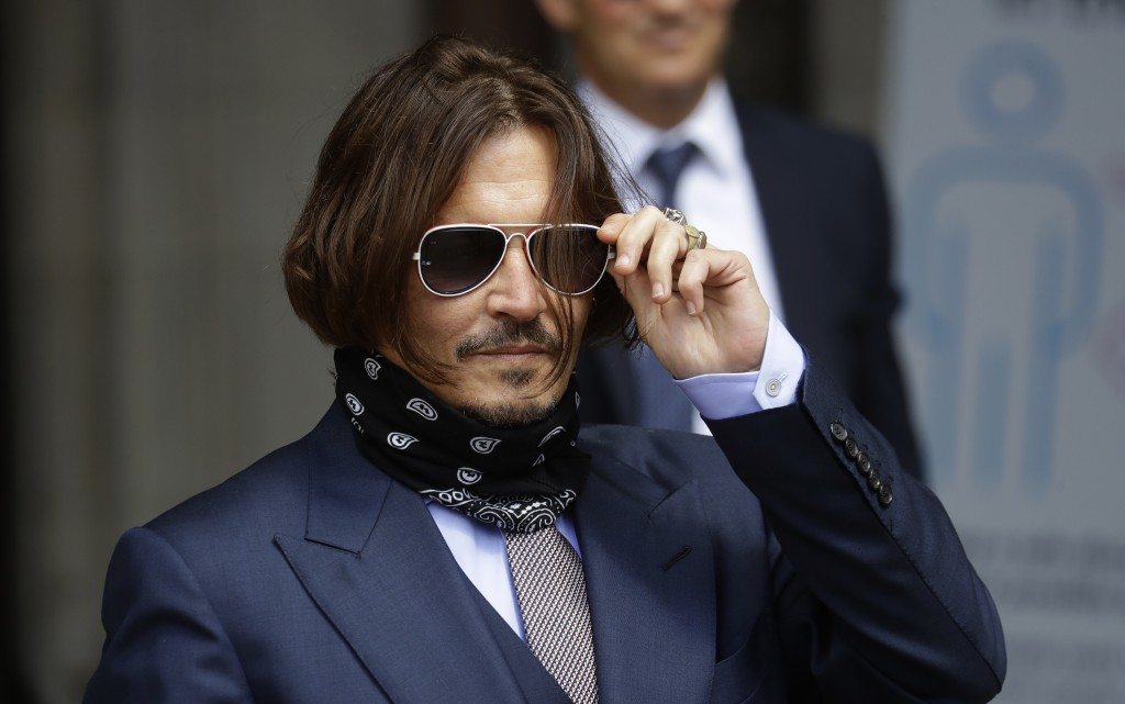 Actor Johnny Depp adjusts his glasses as he arrives at the High Court in London, Friday, July 17, 2020. Depp is suing News Group Newspapers, publisher...