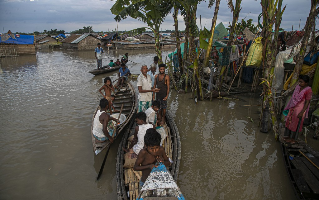 Indian flood affected people take shelter on boats near their submerged houses along river Brahmaputra in Morigaon district, Assam, India, Thursday, J...
