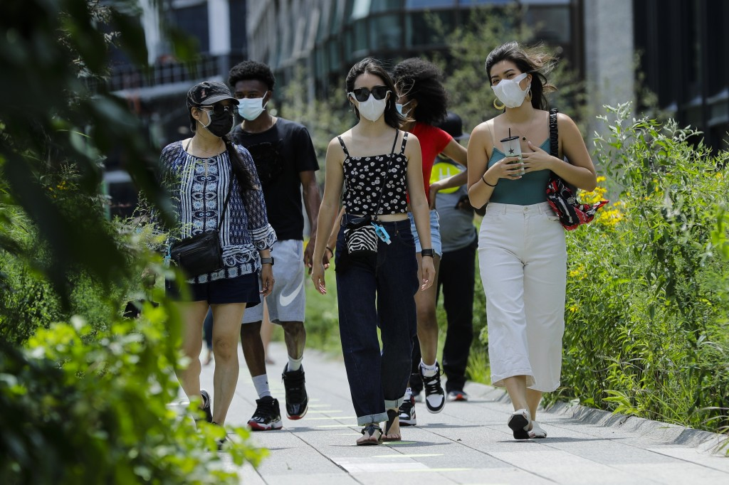 People wearing protective masks during the coronavirus pandemicwalk along the High Line Park, Thursday, July 16, 2020, in New York. The Highline opene...
