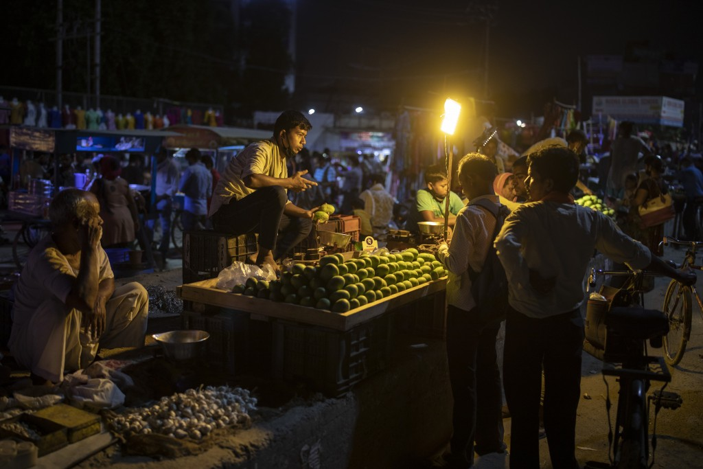 A roadside fruit vendor speaks to his customers, all without masks, at a daily evening market in Noida, on the outskirts of New Delhi, India, Thursday...