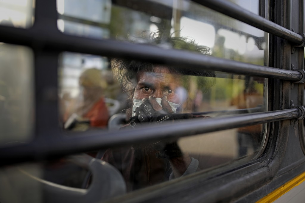An Indian homeless man sits in a bus as he is being evicted with other homeless people and migrant laborers from the banks of Yamuna River where they ...