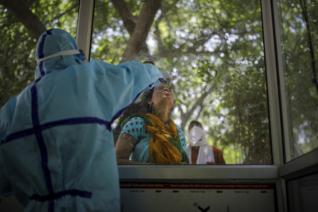 A woman gets a nasal swab taken to test for the coronavirus in Noida, outskirts of New Delhi, India, Thursday, July 16, 2020. (AP Photo/Altaf Qadri)
