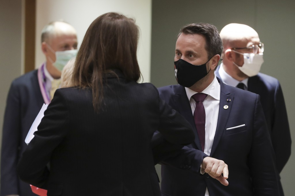 Luxembourg's Prime Minister Xavier Bettel, center, greets Belgium's Prime Minister Sophie Wilmes with an elbow bump during a round table meeting at an...