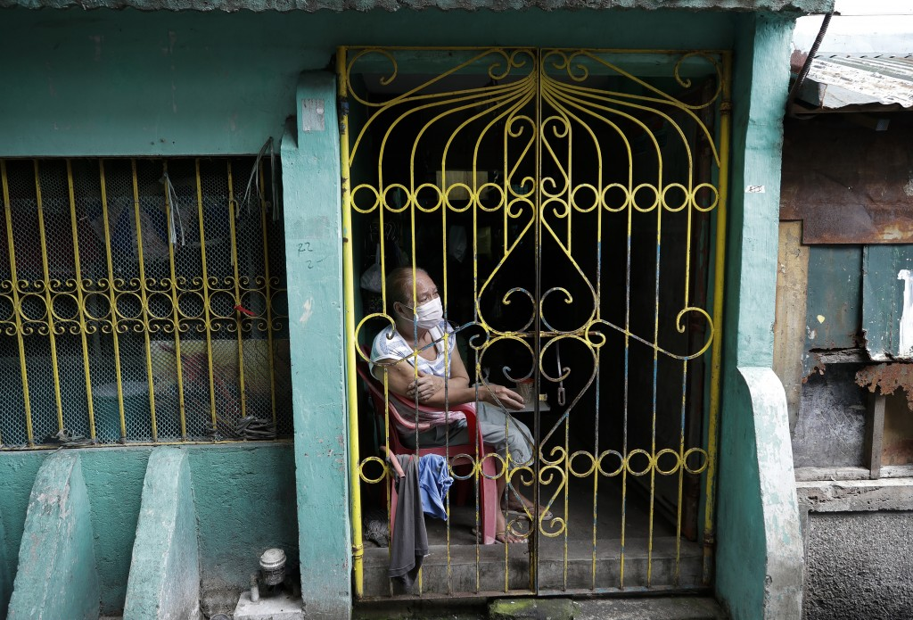 A resident sits inside her home during the start of a lockdown due to a rise in COVID cases in the city of Navotas, Manila, Philippines, Thursday, Jul...