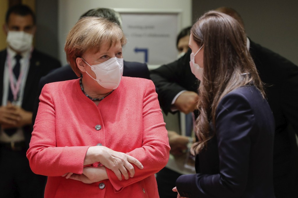German Chancellor Angela Merkel, left, speaks with Finland's Prime Minister Sanna Marin during a round table meeting at an EU summit in Brussels, Frid...