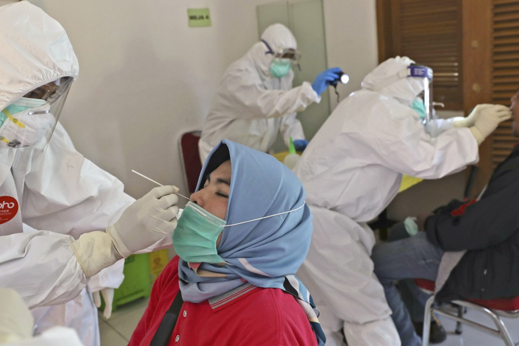 A health worker collects nasal swab samples from a woman during a mass test for the new coronavirus in a neighborhood in Tangerang, Indonesia, Friday,...