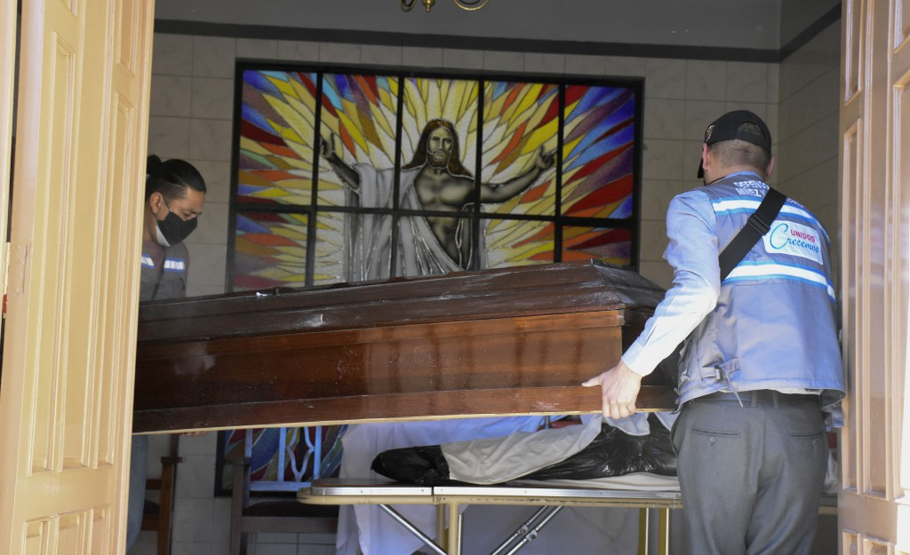 Health workers carry an empty coffin into the San Jose nursing home to recover the body of an recently deceases resident, in Cochabamba, Bolivia, Thur...
