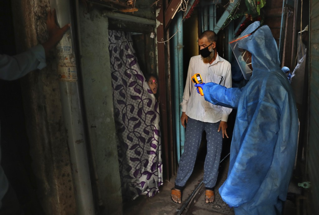 A doctor checks the temperature of a girl in Dharavi, one of Asia's largest slums, during lockdown to prevent the spread of the coronavirus in Mumbai,...