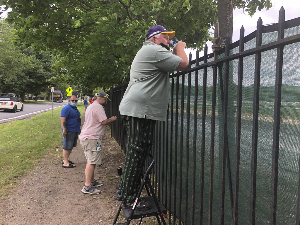 A fan uses a step-stool so he can see horse racing action above the fence at the Saratoga Race Course in Saratoga Springs, N.Y. , Thursday, July 16, 2...