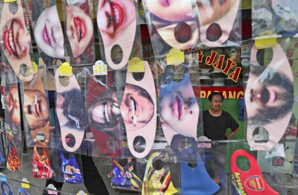 A man is seen through a display of fun face masks for sale at a roadside stall in Jakarta,Indonesia, Thursday, July 16, 2020. Indonesia has the highes...