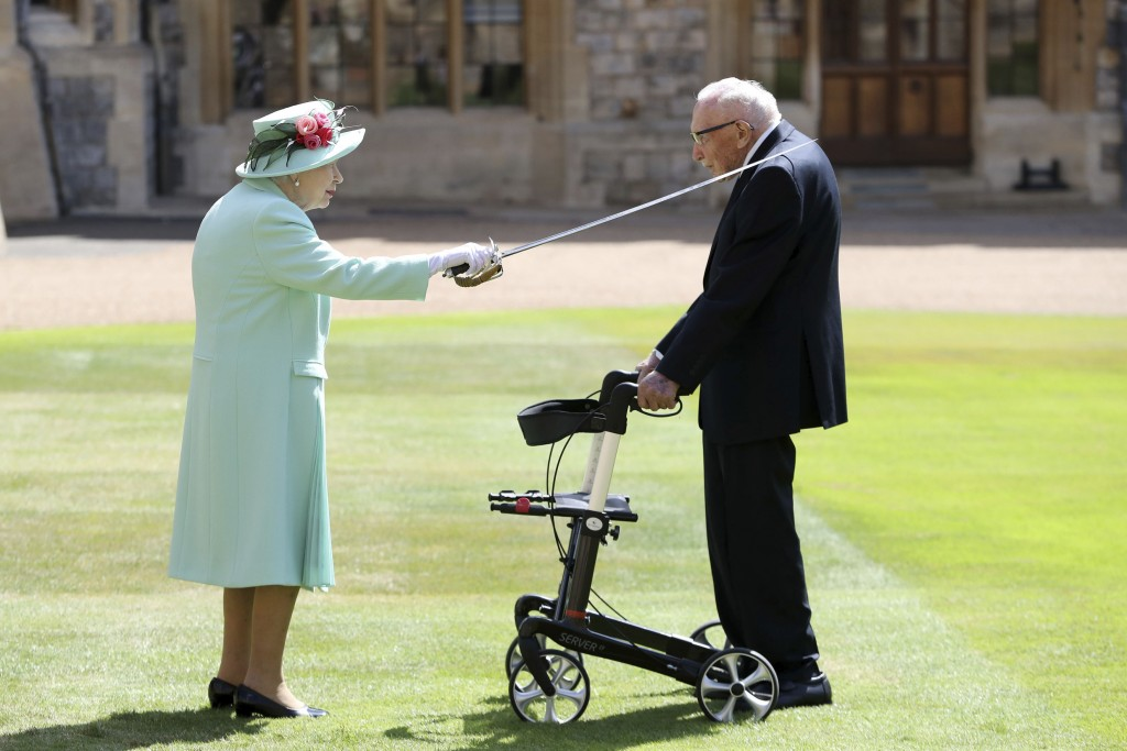 Captain Sir Thomas Moore receives his knighthood from Britain's Queen Elizabeth, during a ceremony at Windsor Castle in Windsor, England, Friday, July...