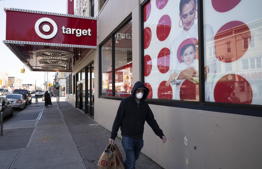 FILE - In this April 6, 2020 file photo, a customer wearing a mask carries his purchases as he leaves a Target store during the coronavirus pandemic i...
