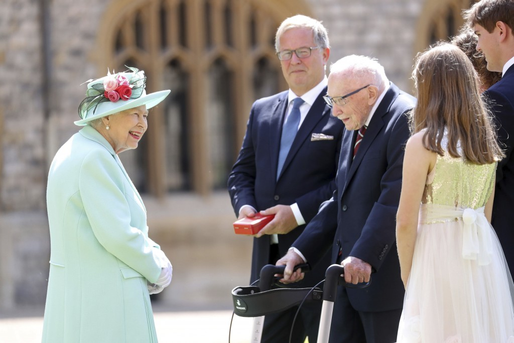 Britain's Queen Elizabeth talks with Captain Sir Thomas Moore and his family after awarding his knighthood during a ceremony at Windsor Castle in Wind...