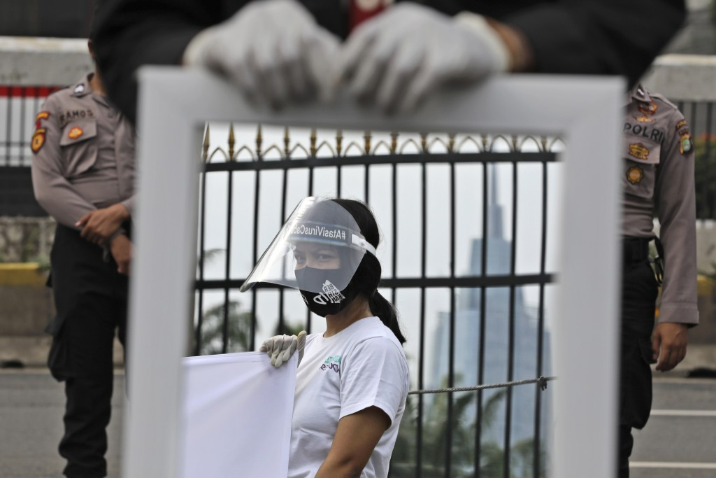 A mirror reflects the image of an activist wearing a mask and protective face shield as a precaution against the new coronavirus outbreak during a sma...