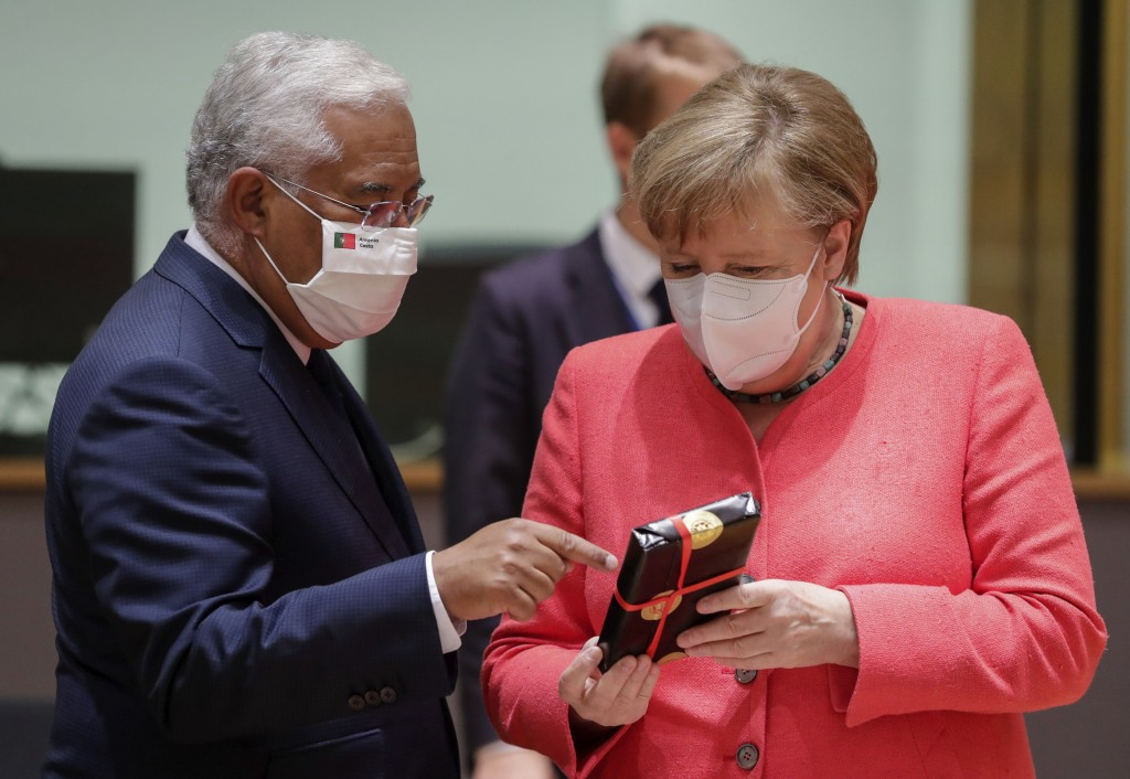 German Chancellor Angela Merkel, right, receives a gift from Portugal's Prime Minister Antonio Costa during a round table meeting at an EU summit in B...