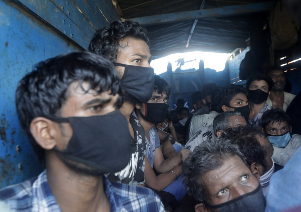 Migrant workers who were traveling in a truck to return to their home state of Uttar Pradesh are detained by police in Mumbai, India, Saturday, May 9,...