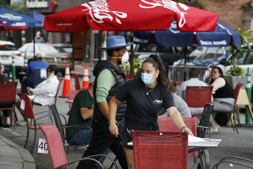 A waitress seats customers at a restaurant with outdoor dining on a section of street closed to traffic to promote social distancing, Friday, July 17,...