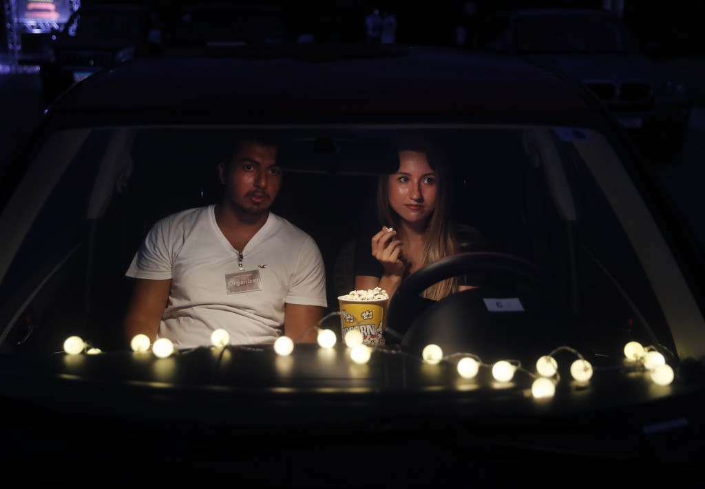 """A couple sit on their car watch """"Hours"""" at a drive-in movie event at a park, in Byblos town, north of Beirut, Lebanon, Friday, July 17, 2020. A group ..."""