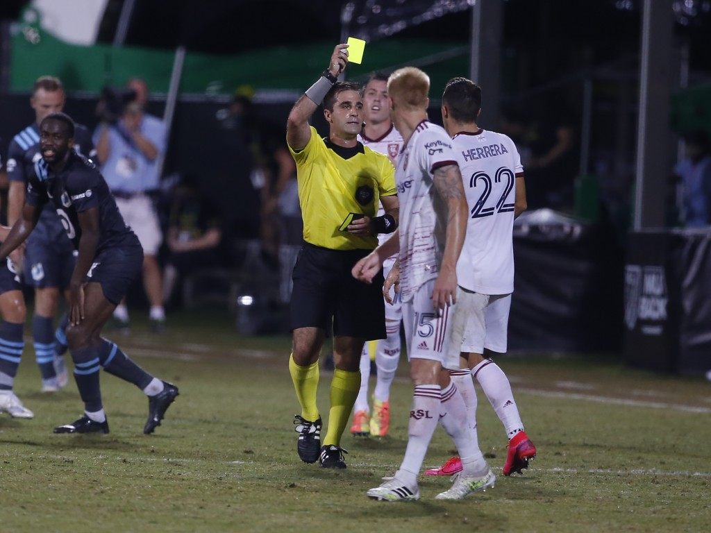 Referee Alex Cailowicz, center, issues a yellow card to Real Salt Lake defender Aaron Herrera (22) as defender Justen Glad (15) looks on during the fi...