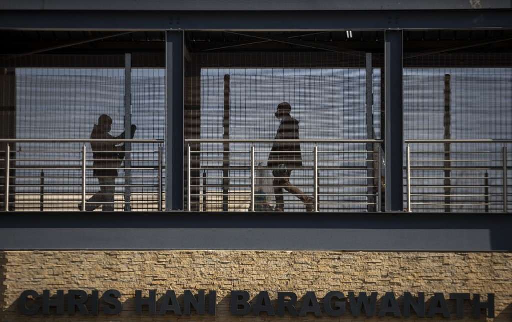 People walk along a skywalk to Chris Hani Bardgwanath Hospital in the township of Soweto in Johannesburg, South Africa, Saturday, July 18, 2020. (AP P...