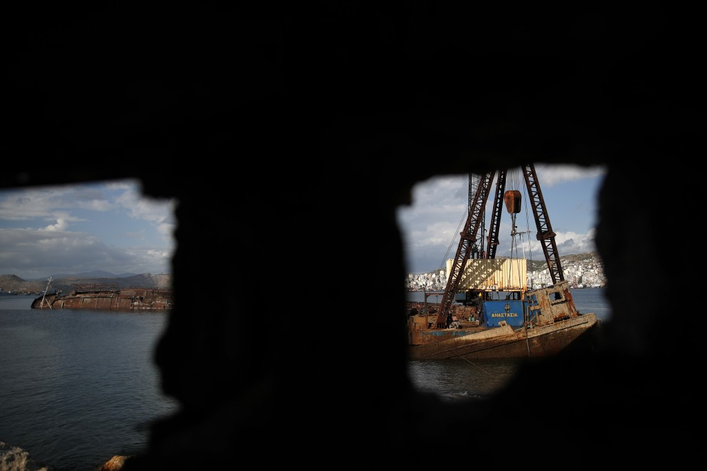 A floating crane holds an old vessel in Damari, an area with eleven shipwrecks, during shipwreck raising operation on Salamina island, west of Athens,...