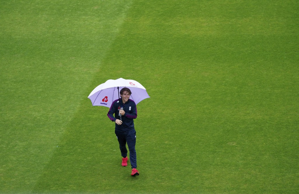 England's Sam Curran walks in the field with an umbrella after rain delayed start of the third day of the second cricket Test match between England an...
