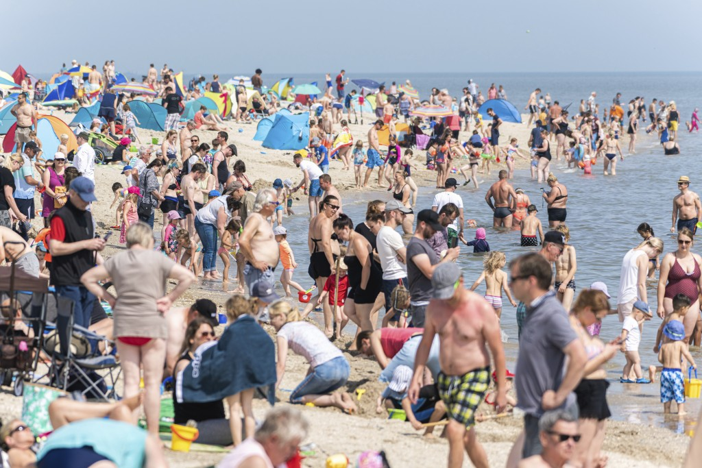 Numerous beach visitors are at summery temperatures on the North Sea beach of Schillig, Germany, Saturday, July 18, 2020. (Mohssen Assanimoghaddam/dpa...
