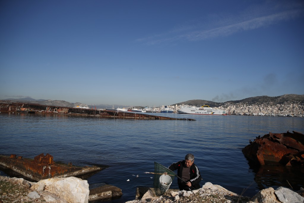 A man holds a bucket with fish in Damari, an area with eleven shipwrecks, on Salamina island, west of Athens, on Thursday, Jan. 31, 2020. Greece this ...
