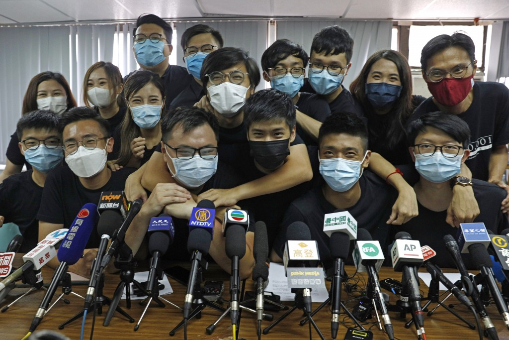 Pro-democracy activists who were elected from unofficial pro-democracy primaries, including Joshua Wong, left, gather during a news conference in Hong...