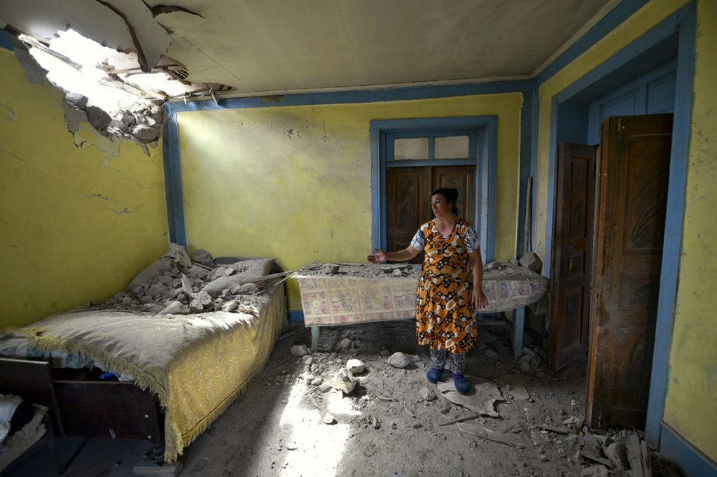 A woman shows damage to her house after shelling by Armenian forces in the Tovuz region of Azerbaijan, Tuesday, July 14, 2020. Skirmishes on the volat...