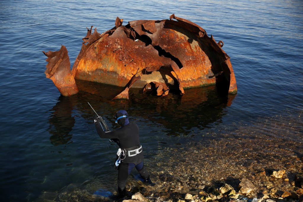 An amateur fisherman with speargun prepares to dive next to a part of shipwreck in Damari, an area with eleven shipwrecks, on Salamina island, west of...