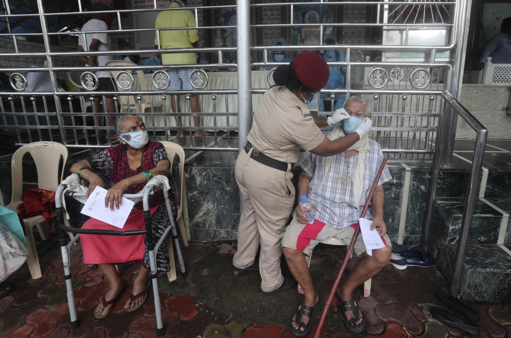 A police officer helps an elderly man put on a face mask, as he waits for a consultation with health officers at a temple in Mumbai, India, Saturday, ...