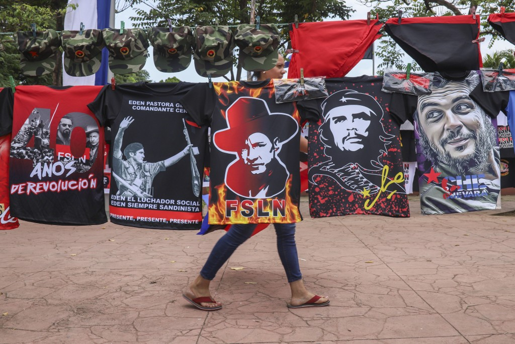 A woman walks past T-shirts for sale promoting The Sandinista National Liberation Front ruling party on the sidelines of a new monument, called the Pe...