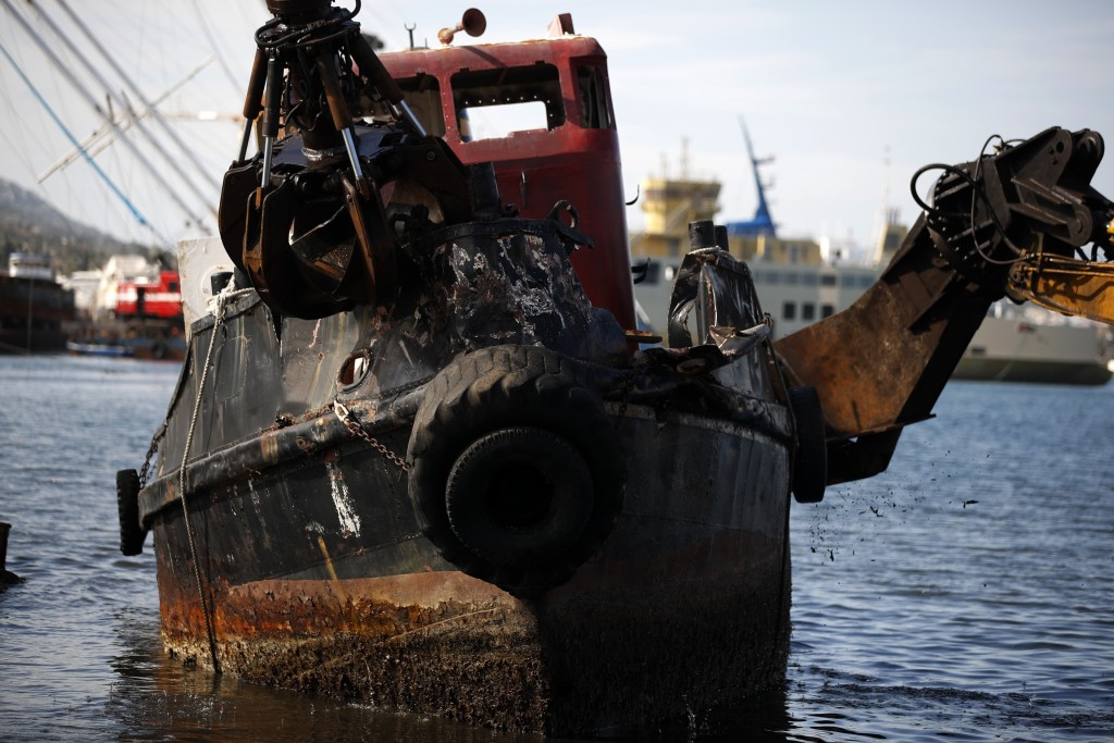 Heavy machinery destroys an abandoned boat on Salamina island, west of Athens, on Tuesday, Feb. 12, 2020. Greece this year is commemorating one of the...