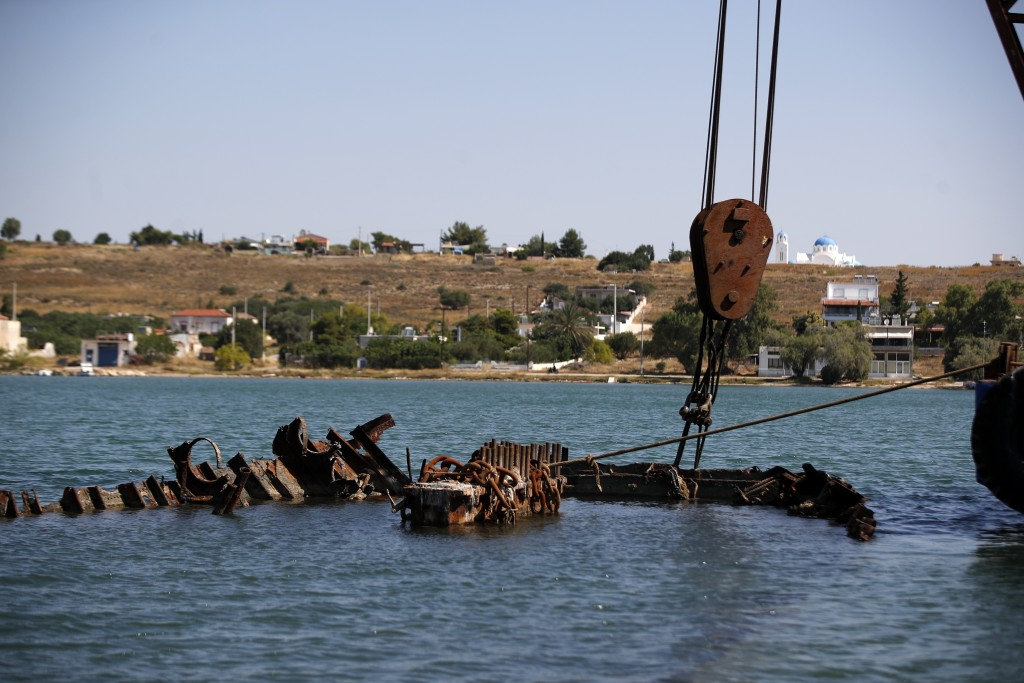 A floating crane holds a shipwreck before the raising operation on Salamina island, west of Athens, on Wednesday, June 29, 2020. Greece this year is c...