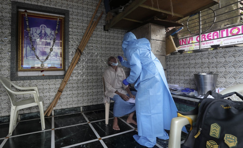 A health worker takes a swab test at a temple in Mumbai, India, Saturday, July 18, 2020. India crossed 1 million coronavirus cases on Friday, third on...