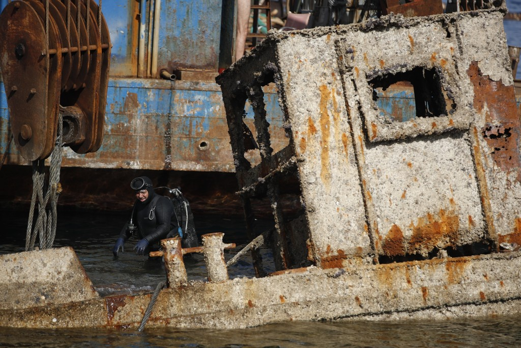 A diver checks an old vessel during a shipwreck raising operation, on Salamina island, west of Athens, on Friday, Nov. 8, 2019. Greece this year is co...