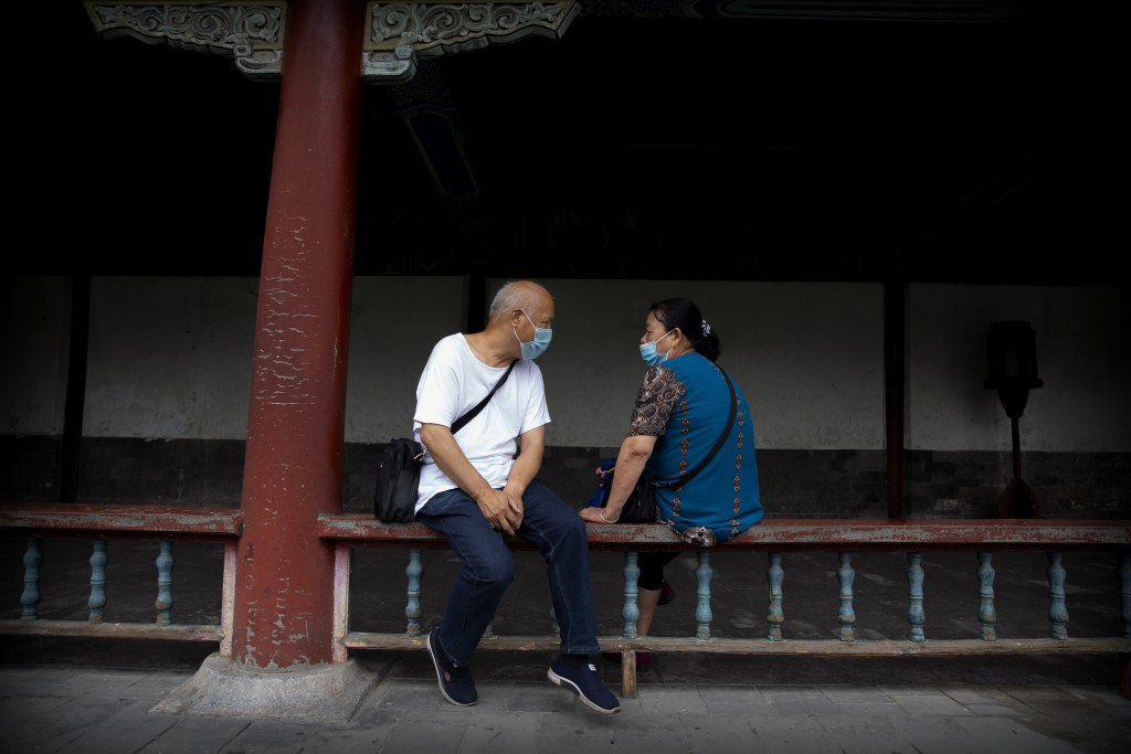 People wearing face masks to protect against the coronavirus sit on a railing at the Temple of Heaven in Beijing, Saturday, July 18, 2020. Authorities...