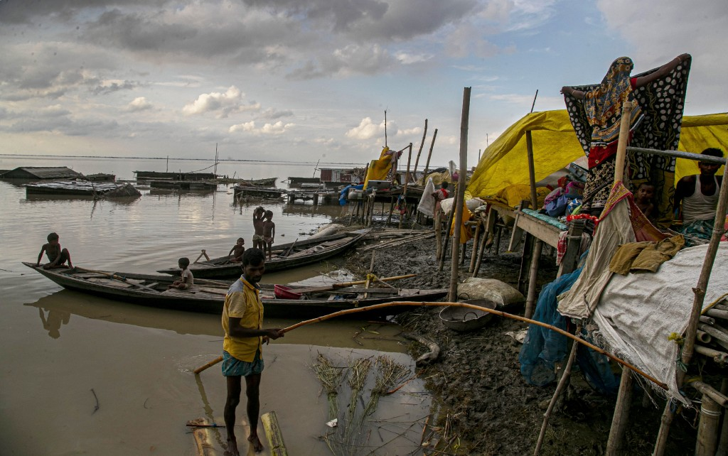 Flood affected people take shelter at temporary structures near their submerged home along the Brahmaputra River in Morigaon district, Assam, India, T...