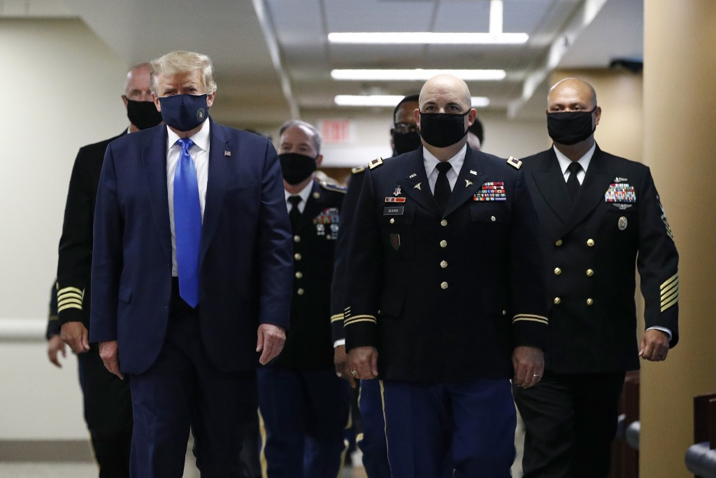 President Donald Trump, foreground left, wears a face mask as he walks with others down a hallway during a visit to Walter Reed National Military Medi...