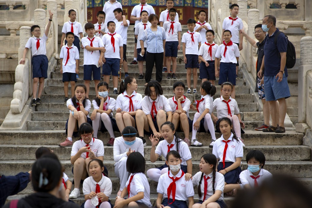 Students wearing face masks to protect against the coronavirus sit on steps at the Temple of Heaven in Beijing, Saturday, July 18, 2020. Authorities i...